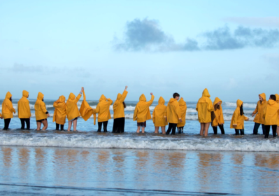 High Tide Don't Hide students standing in a line in yellow rain jackets holding hands in the air. All standing in the tide facing out to sea.